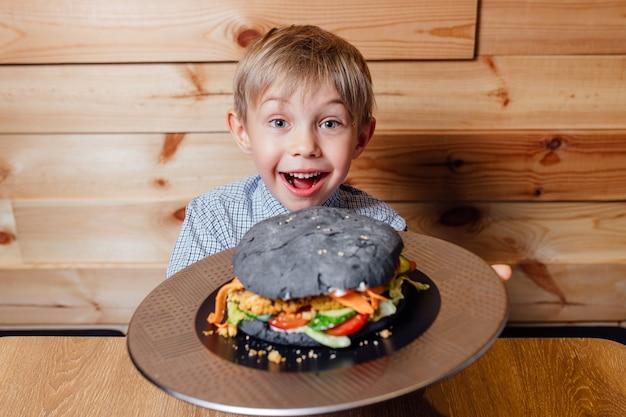 Piccolo bambino felice con hamburger nero vegetariano, esaminando la fotocamera, sfondo wog
