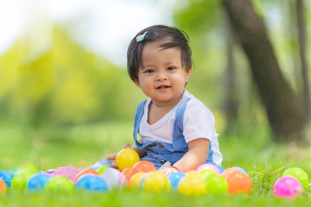 Piccolo bambino felice e palle colorate nel parco