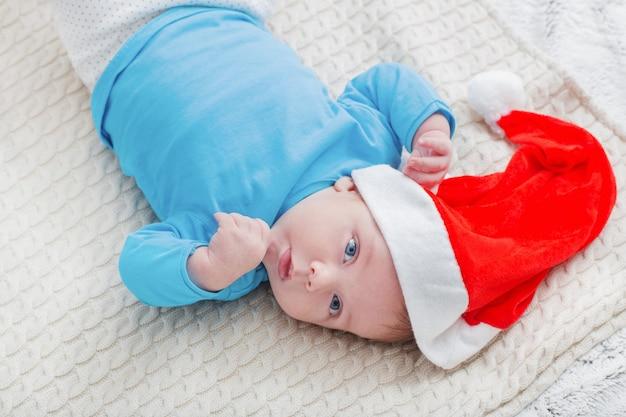 Piccolo bambino in cappello rosso della santa