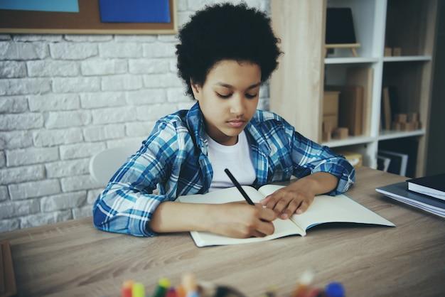 Piccolo bambino in età prescolare africano che fa i compiti che si siedono alla tavola.