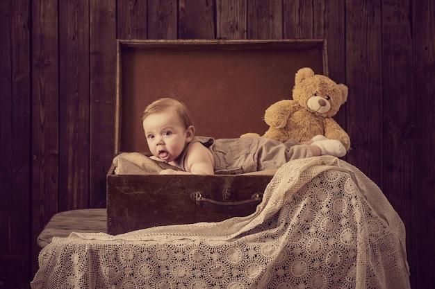 Piccolo bambino in valigia su legno