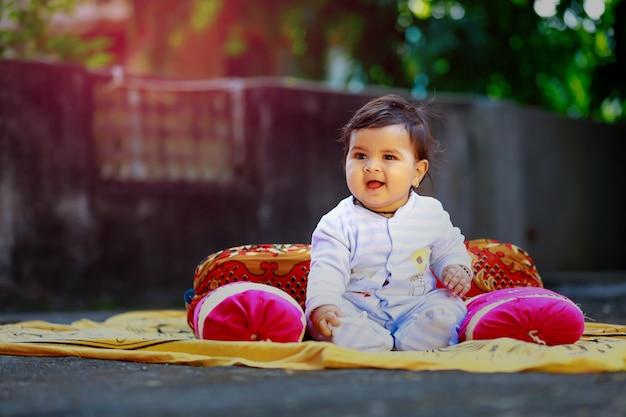 Piccolo bambino indiano sveglio che sorride e che gioca davanti alla casa