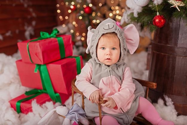 Piccolo bambino (ragazza) in abito festivo di topo (ratto) si siede su slitte vicino all'albero di natale con decorazioni natalizie e regali