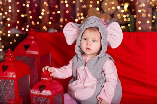 Piccolo bambino (ragazza) in abito festivo di topo (ratto) si siede vicino a torce e decorazioni natalizie