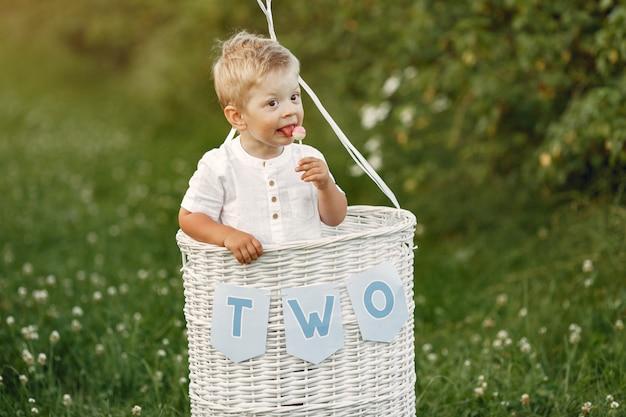 Piccolo bambino seduto nel cestino con palloncini