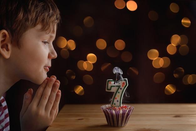 Piccolo bambino sveglio che soffia le candele sulle torte di compleanno.