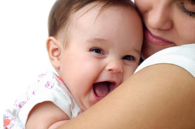 Piccolo bambino sveglio che sorride sulla spalla delle madri