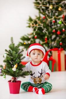 Piccolo bambino sveglio della santa in pigiama bianco e verde. albero di natale e regali di capodanno sul