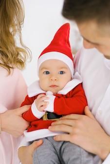 Piccolo bambino sveglio in cappello e costume di santa con i loro genitori