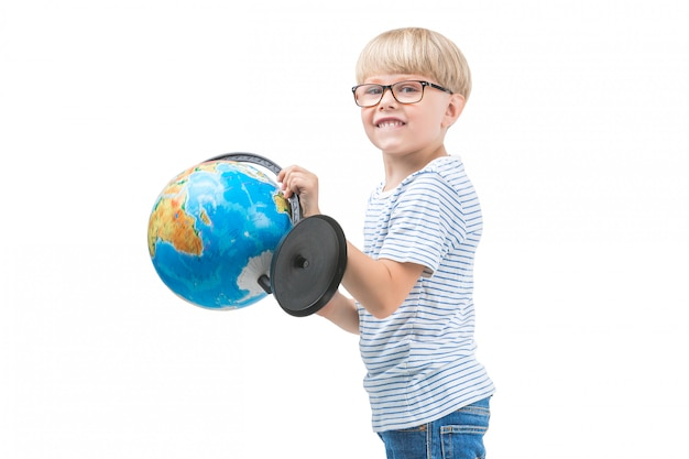 Piccolo bambino sveglio isolato sul globo bianco della tenuta del fondo. scolaro studia geografia. viaggio ragazzo carino. vacanze in famiglia con bambini
