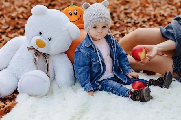 Piccolo bambino sveglio nel parco sulla foglia gialla con la zucca in autunno