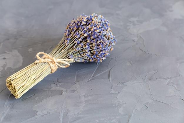 Piccolo bouquet carino di profumata lavanda secca legata con filo su un tavolo grigio