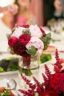 Piccolo bouquet di peonie si erge in un vaso alto con acqua