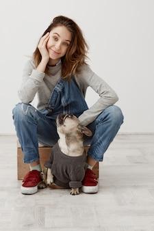 Piccolo cane e donna carina con fluenti capelli castani seduto sulla scatola tenendo la testa con la mano. proprietario femminile dell'animale domestico che prende piacere in compagnia del suo bulldog francese. concetto di amicizia
