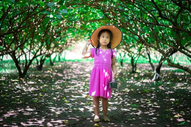 Piccolo cappello asiatico di usura della ragazza che guarda la frutta del gelso nel giardino