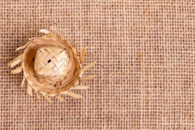 Piccolo cappello di paglia utilizzato per gli ornamenti di festa junina su un tavolo con tessuto di iuta.