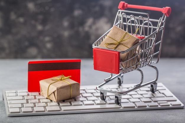 Piccolo carrello con regali e carta di credito su concetti di tastiera di un computer portatile