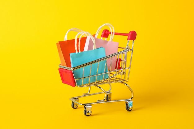 Piccolo carrello con sacchi di carta su spazio giallo, spazio per il testo