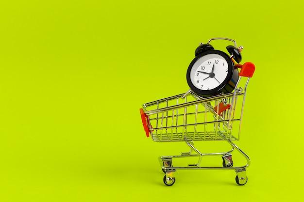 Piccolo carrello con sveglia. concetto di tempo di shopping