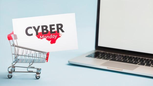 Piccolo carrello del supermercato con grande etichetta e laptop