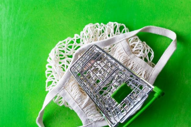 Piccolo carrello sopra la borsa a rete sul verde