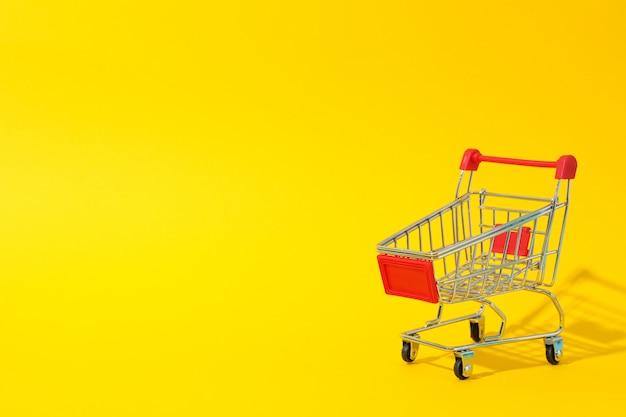 Piccolo carrello su spazio giallo, spazio per il testo