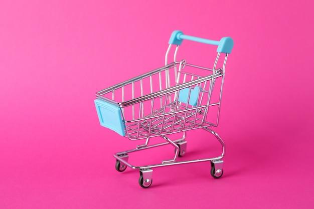 Piccolo carrello su spazio rosa, spazio per il testo