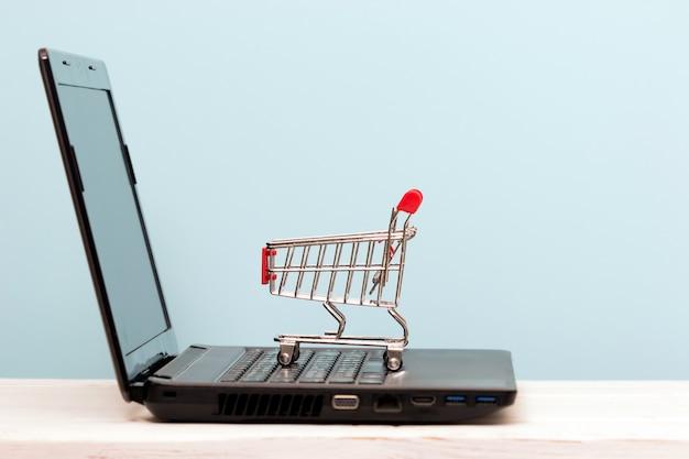 Piccolo carrello sul portatile per lo shopping online. concetto online di tecnologia aziendale.