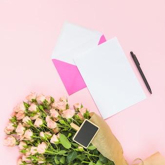 Piccolo cartello sul bouquet con carta bianca vuota; penna e busta su sfondo colorato