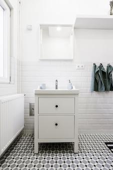 Piccolo cassetto bianco in un bagno bianco con articoli per l'igiene