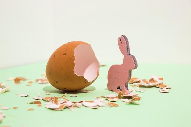 Piccolo coniglio in legno con uovo rotto sul tavolo