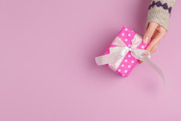 Piccolo contenitore di regalo in mani femminili, vista da sopra