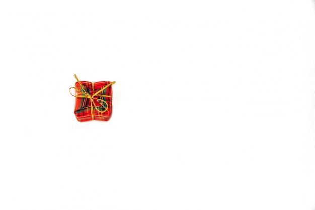 Piccolo contenitore di regalo rosso con il nastro rosso su fondo bianco