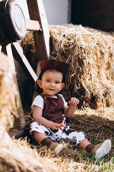 Piccolo cowboy seduto sul fieno