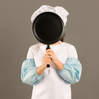 Piccolo cuoco unico che tiene padella di cottura