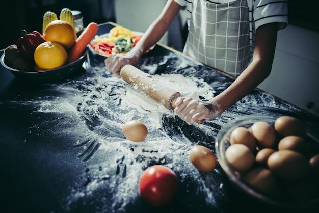 Piccolo cuoco unico che utilizza il matterello che allunga la pasta. concetto di cottura.
