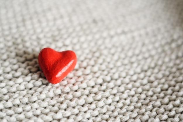 Piccolo cuore rosso su un primo piano del fondo tricottato. posto per il testo