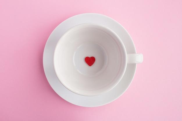 Piccolo cuore rosso sulla tazza bianca vuota sui precedenti rosa vista superiore copi lo spazio concetto minimo diabolico.