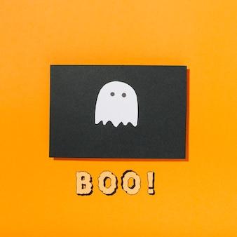 Piccolo fantasma su un pezzo di carta nera con boo! iscrizione