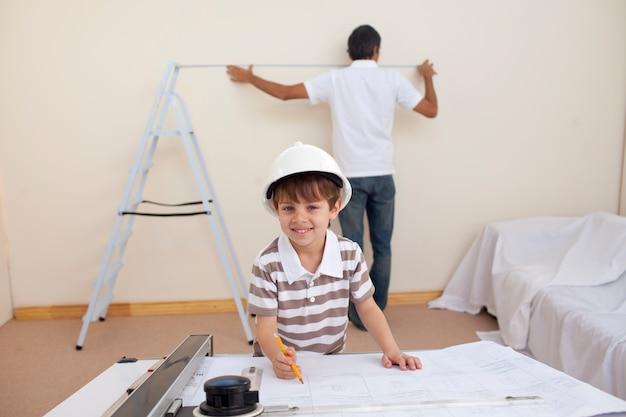Piccolo figlio che disegna piani e padre che lavora