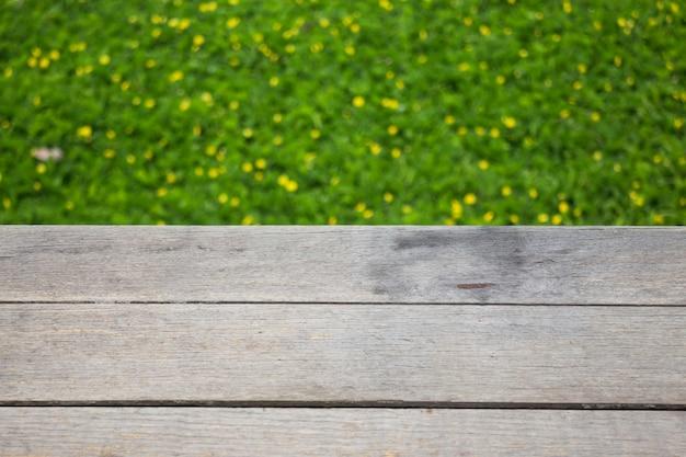 Piccolo fiore giallo su erba verde con fondo di legno