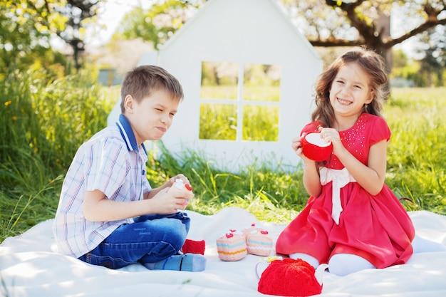 Piccolo fratello e sorella tè in giardino. il concetto di infanzia e stile di vita.