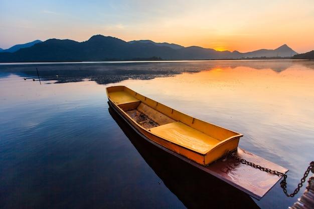 Piccolo galleggiante della barca del pescatore sul lago con il cielo di alba