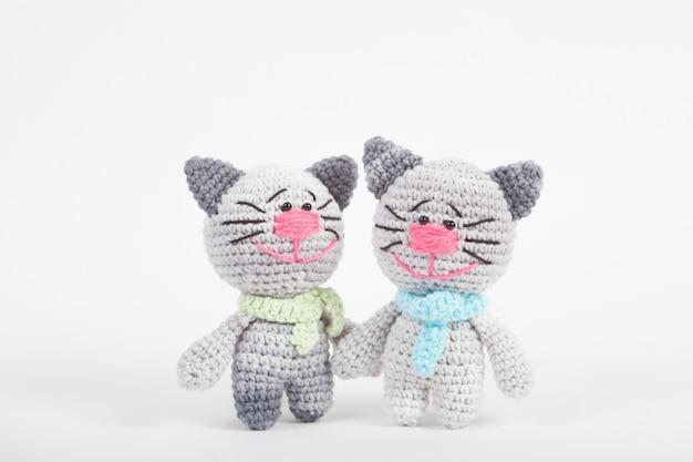 Piccolo gatto a maglia su uno sfondo bianco. giocattolo lavorato a mano. amigurumi