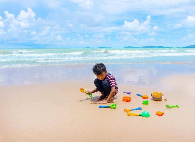 Piccolo gioco asiatico del ragazzo con la sabbia sulla spiaggia.