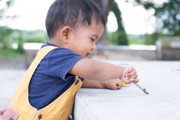 Piccolo gioco sveglio del neonato al parco
