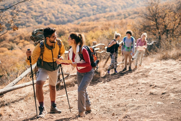 Piccolo gruppo di persone che fanno un'escursione in autunno. in primo piano coppia guardando la mappa e in background resto del gruppo.