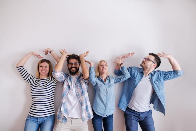 Piccolo gruppo di persone che sollevano le mani in aria come se avessero qualcosa in mano. avviare il concetto di business.