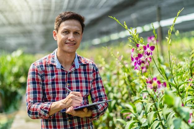 Piccolo imprenditore asiatico del ritratto dell'azienda agricola di giardinaggio dell'orchidea