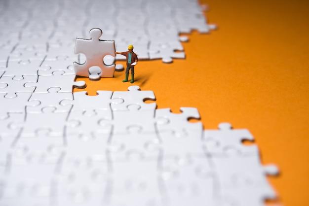 Piccolo imprenditore in piedi su un puzzle bianco.